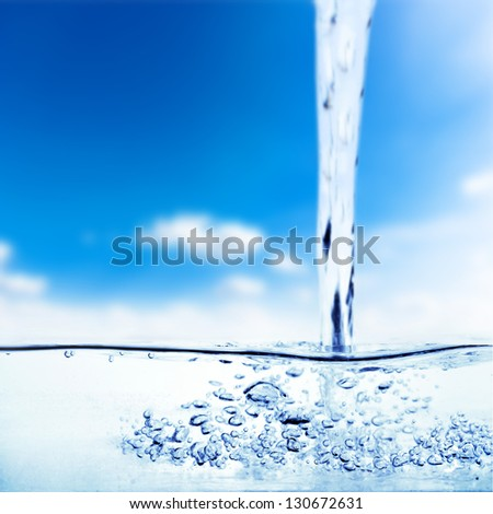 Flowing water and air bubbles over sky background - stock photo