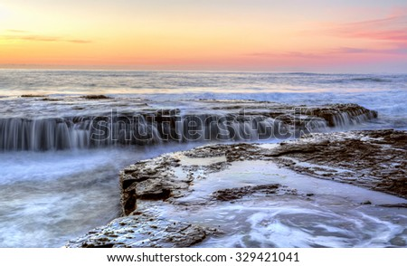 Flowing water over rocks and into the chasm at Coledale NSW Australia at sunrise - stock photo