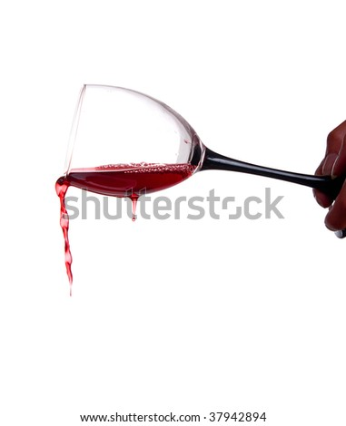 Flowing wine from a wineglass holding in hahds. Isolated on white. - stock photo