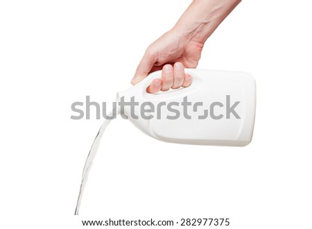 Flows out  liquid from white plastic bottle in hand, isolated on white background - stock photo
