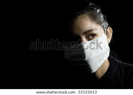 flu alarm: protective face mask on beautiful asian woman. low-key picture. - stock photo