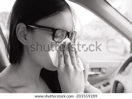 Flu cold or allergy symptom. Sick woman girl sneezing in tissue in the car. Health care. - stock photo