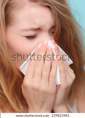 Flu cold or allergy symptom. Sick woman girl sneezing in tissue on blue. Health care. - stock photo