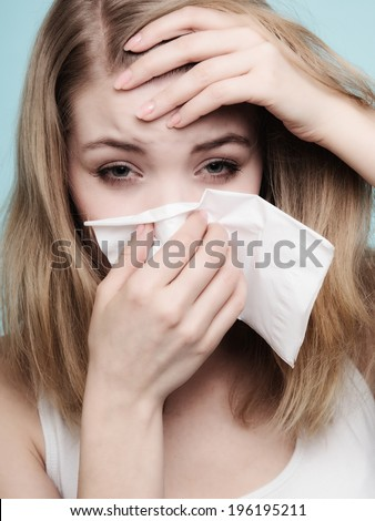 Flu cold or allergy symptom. Sick woman girl with fever sneezing in tissue on blue. Health care. - stock photo