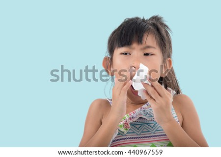 Flu cold or allergy symptom.Sick young asian girl with fever sneezing in tissue,allergies,the common cold,with blank copy space on blue - stock photo