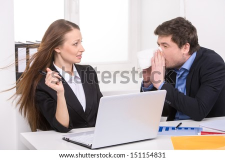 Flu. Man sneezing while sitting near his coworker - stock photo