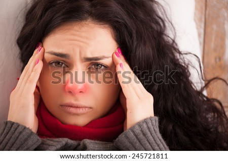 Flu or cold. Closeup top view image of frustrated young woman with red nose and suffering from terrible headache while lying in bed - stock photo
