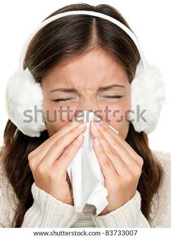 Flu or cold - sneezing woman sick blowing nose. Young woman being cold wearing earmuffs and sweater. Asian Caucasian female model. - stock photo