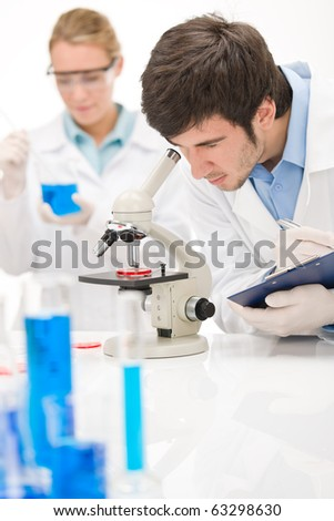 Flu virus experiment -  scientist in laboratory with microscope, wear protective eyewear - stock photo
