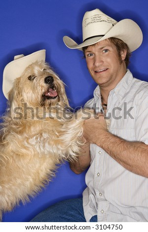 Fluffy brown dog and male Caucasian young adult wearing cowboy hats. - stock photo