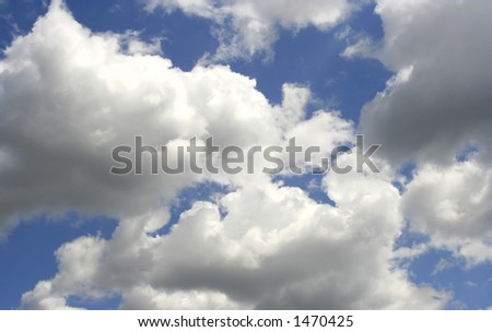 Fluffy clouds against a clear, bright , blue sky