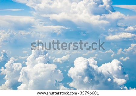 Fluffy clouds shot from airplane window - stock photo