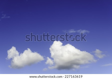 Fluffy cumulus clouds against blue sky - stock photo