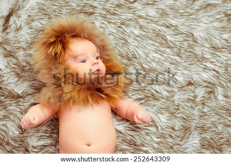 Fluffy cuttie. Top view of an adorable baby wearing a fur hat and lying on the fur blanket - stock photo