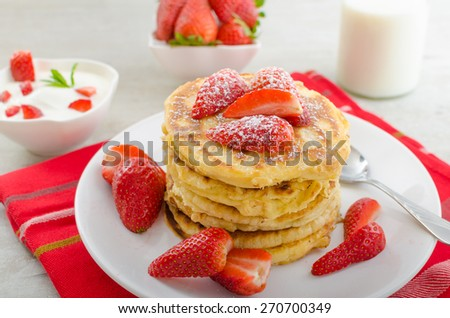 Fluffy pancakes with strawberries, sprinkled with sugar, with healthy milk and creamy dip - stock photo