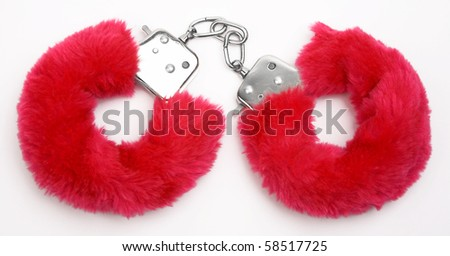 fluffy pink handcuffs on white background - stock photo