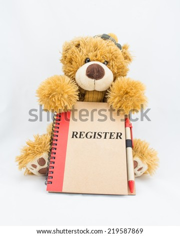"Fluffy teddy bear holding a notebook with the words ""REGISTER"" - stock photo"
