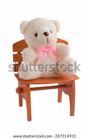 Fluffy teddy bear isolated on white background with brown chair. - stock photo