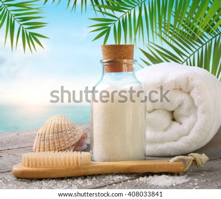 Fluffy towels with sea salt and seashells on beach table - stock photo