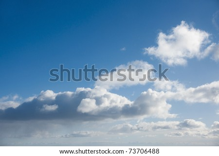 Fluffy white clouds in blue sky - stock photo