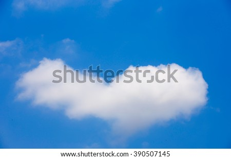 Fluffy white clouds shaped like a heart. On the blue sky.