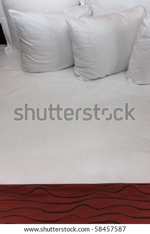 Fluffy white pillows against a white sheet with a red blanket. - stock photo
