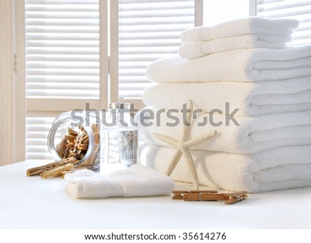Fluffy white towels on table with shutter doors - stock photo