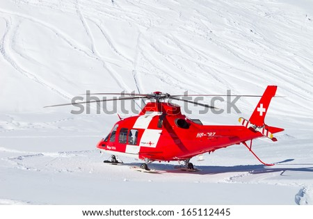FLUMSERBERG - FEBRUARY 21: The rescue helicopter evacuates skiier after heavy accident, Flumserberg, Switzerland on February 21, 2010. Skiing safety becoming an issue on crowded slopes. - stock photo