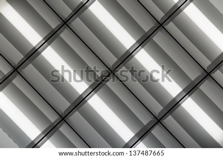 fluorescent lamps lighted fixed to the ceiling. Geometry and style - stock photo