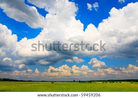 Flurry cumulus clouds and green meadow below. - stock photo