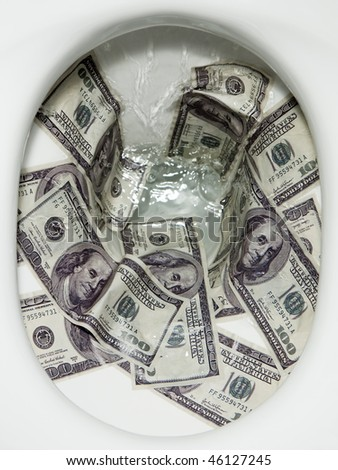 Flushing dollar bills into a toilet bowl - stock photo