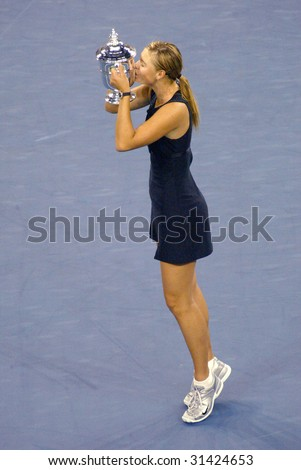 FLUSHING, NY - SEPT 9: Maria Sharapova (RUS) kisses her trophy after beating Justine Henin-Hardenne (BEL) to win the ladies singles final at the U.S. Open on September 9, 2006 in Flushing, New York. - stock photo