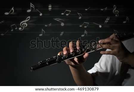Flute music playing flutist musician performer with music notes or melody on dark background, musical instrument concept
