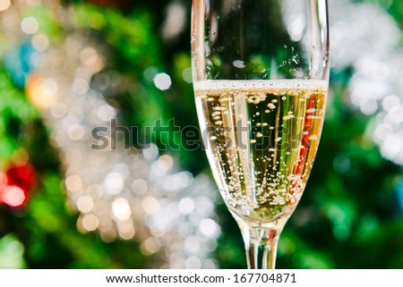 Flute of champagne in holiday setting, focus on  foreground - stock photo