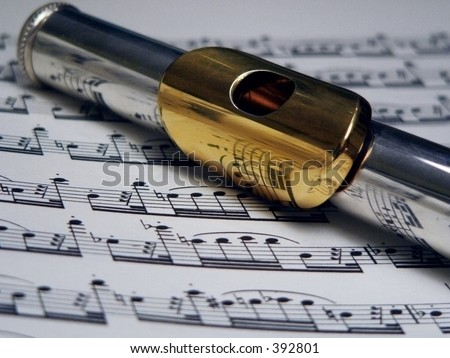 flute with gold mouthpiece on sheet music - stock photo