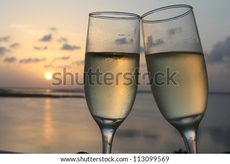Flutes of champagne with sunset background - stock photo