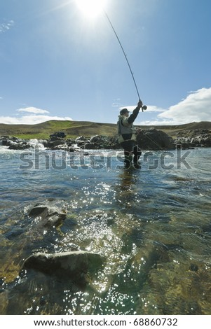 Fly fisherman casting the fly in beautiful surroundings in Iceland - stock photo
