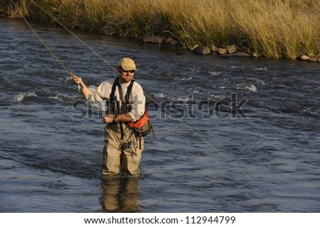 Fly-fisherman casting to trout on the Umzimkulu river,Underberg,Southern drakensberg, Kwazulu natal, South Africa.  The Umzimkulu lies at the heartland of South Africa's trout fishing region - stock photo