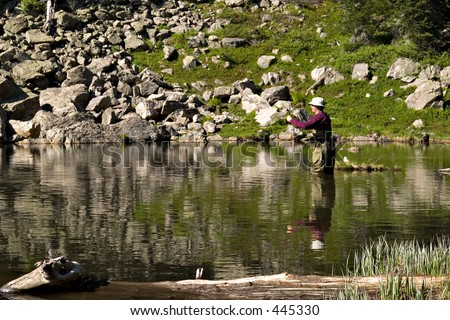 Fly fisherman fishing for trout in a mountain lake (horizontal) - stock photo
