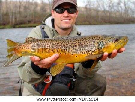 Fly fisherman holding a huge Brown Trout fish prior to releasing into the river - stock photo