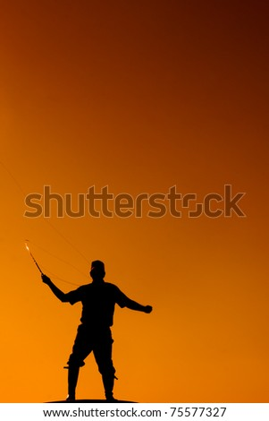 Fly fisherman in silhouette - stock photo