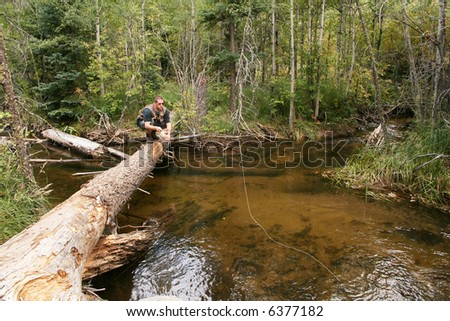 Fly Fisherman on log across stream - stock photo