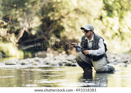 Fly fisherman using flyfishing rod in beautiful river.