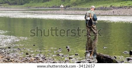 Fly fishermen at a lake - stock photo