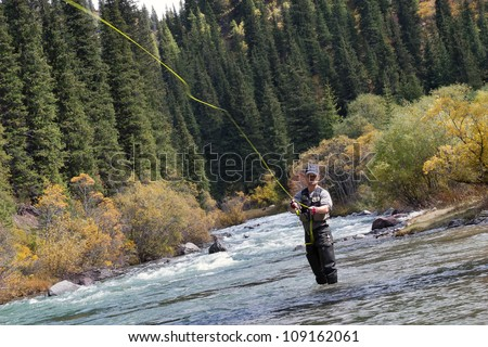 fly fishing angler makes cast while standing in water - stock photo