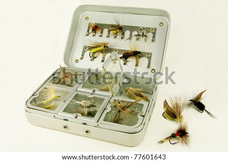Fly Fishing Box:  A well-used tackle box displays a variety of handmade lures for fly-fishing. - stock photo