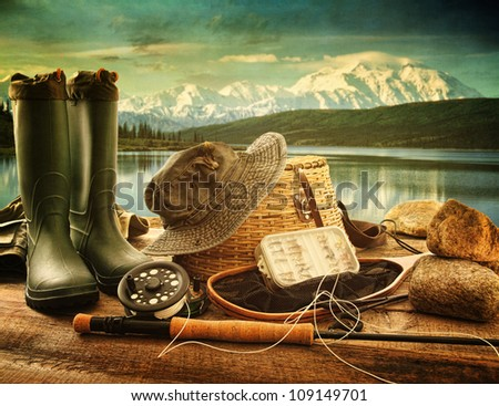 Fly fishing equipment on deck with beautiful view of a lake and mountains - stock photo