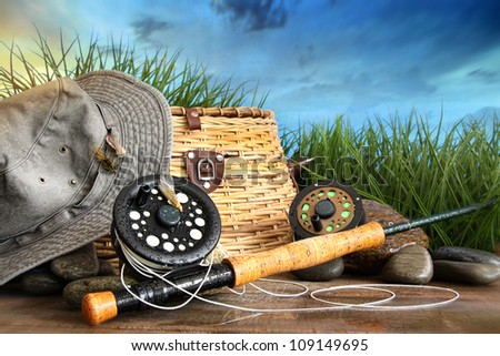 Fly fishing equipment with hat on wooden dock in grass - stock photo
