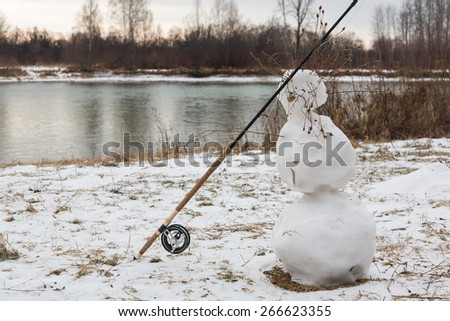Fly fishing, fish, fishing rod in the snow. grayling - stock photo