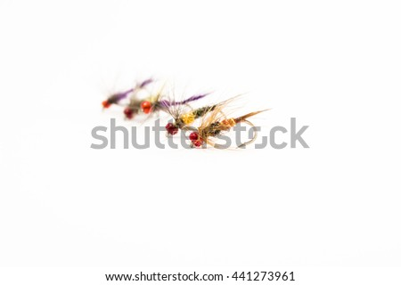 Fly fishing flies close-up front view on a uniform white background. One of the essential elements of fishing equipment or tackle for fly fishing - stock photo